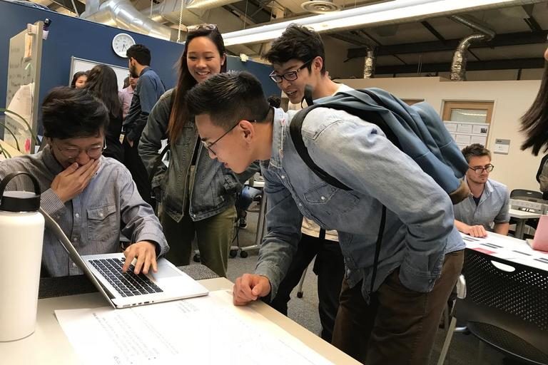 Four students gathering around a laptop, laughing, at the Spring 2018 semester Data Scholars project showcase.