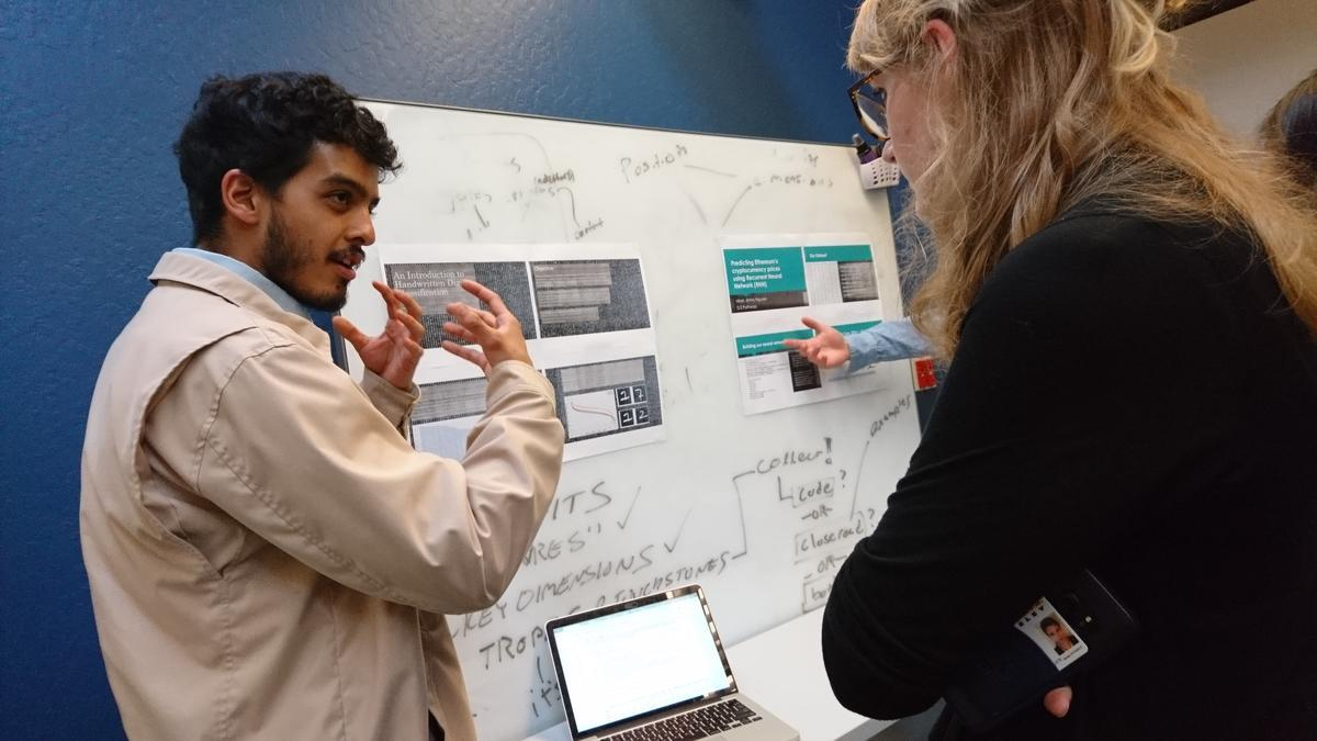 a student presenting their research project to another student at the spring 2018 data scholars project showcase